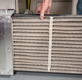 Senior man changing a dirty air filter in a HVAC Furnace. Senior caucasian man changing a folded dirty air filter in the HVAC furnace system in basement of home stock photography