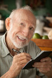 Senior man with checkbook. Senior man at home with checkbook royalty free stock photos