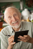 Senior man with checkbook. Senior man at home with checkbook stock photography