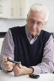 Senior Man Checking Blood Sugar Level At Home Royalty Free Stock Images