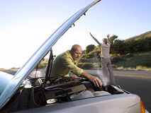 Senior man checking car engine at roadside, woman hailing oncoming traffic on country road Stock Photo