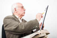 Senior man checking data on clipboard Stock Images