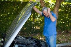 Senior man checking engine of breakdown car Royalty Free Stock Image