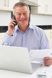 Senior Man Checking Finances On The Phone. Concerned Senior Man Looks At Personal Finances Stock Photos