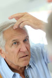 Senior man checking on his hair royalty free stock photo