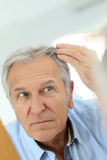 Senior man checking his hair loss Stock Image