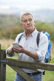 Senior Man Checking Location With Mobile Phone On Hike Stock Photo