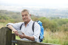 Senior Man Checking Location With Mobile Phone On Hike Stock Image