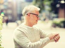 Senior man checking time on his wristwatch stock image