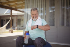 Senior man checking time on wristwatch after work out Royalty Free Stock Photography