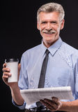 Senior man. Cheerful senior man with coffee and newspaper on dark background royalty free stock images