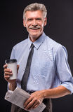 Senior man. Cheerful senior man with coffee and newspaper on dark background royalty free stock photography