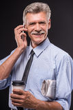 Senior man. Cheerful senior man with coffee and newspaper is talking by phone, on dark background stock photography