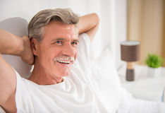 Senior man. Cheerful senior man is sitting in bed and smiling Stock Photography