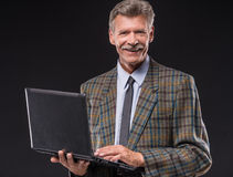 Senior man. Cheerful senior man is standing on dark background and holding laptop stock photos