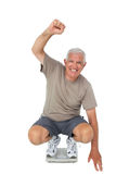 Senior man cheering on weight scale Stock Photos