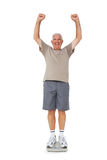 Senior man cheering on weight scale Royalty Free Stock Photos