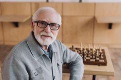 Senior man with chess board. Handsome senior man with chess board sitting in cafe and looking at camera Royalty Free Stock Photography
