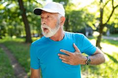 Senior man with chest pain suffering from heart attack during jogging. Man with chest pain suffering from heart attack during running stock photography
