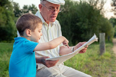 Senior man and child reading a newspaper outdoors Stock Photos