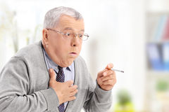 Senior man choking from the smoke of a cigarette Royalty Free Stock Image
