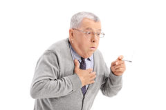 Senior man choking from the smoke of a cigarette Stock Photos