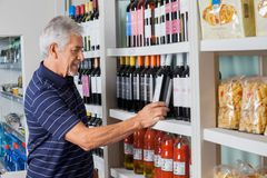 Senior Man Choosing Wine At Supermarket Royalty Free Stock Image