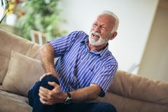 Senior man with chronic knee problems and pain. At home stock photo