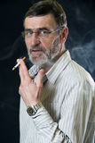 Senior man with cigarette Stock Images
