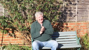 Senior man clapping. A senior man sitting on a bench happy, smiling and clapping his hands stock video