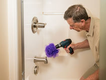 Senior man cleaning a shower with power drill. Senior working man cleaning a shower or bath with a power drill Royalty Free Stock Photography