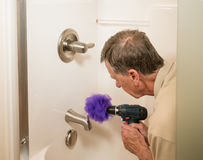 Senior man cleaning a shower with power drill. Senior working man cleaning a shower or bath with a power drill Royalty Free Stock Images