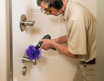 Senior man cleaning a shower with power drill Stock Image