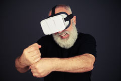 Senior man clenches his fists in virtual reality Stock Photo