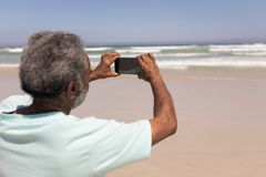 Senior man clicking photo with mobile phone on beach. Rear view of senior man clicking photo with mobile phone on beach in the sunshine stock images