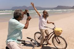 Senior man clicking photo of senior woman with mobile phone on beach. Side view senior men clicking photo of senior women with mobile phone on beach in the stock image