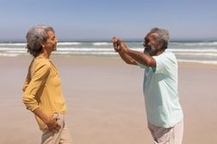 Senior man clicking photo of woman with mobile phone on beach. Side view of senior men clicking photo of women with mobile phone on beach in the sunshine royalty free stock photography