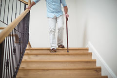 Senior man climbing downstairs with walking stick. At home Royalty Free Stock Images
