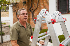 Senior man climbing a ladder. stock images