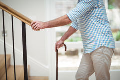 Senior man climbing upstairs with walking stick Stock Photography