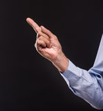 Senior man. Close-up of finger pointing away on dark background stock photo