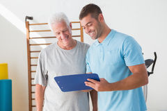 Senior man with coach looking at clipboard Royalty Free Stock Photography