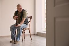 Senior man with coins sitting on chair in empty room. Poverty concept Royalty Free Stock Photos