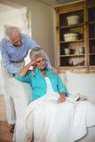 Senior man comforting senior woman in living room Royalty Free Stock Images