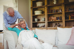 Senior man comforting senior woman in living room Stock Photos
