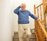 Man with faintness at the stairs home. Senior man coming down the stairs and having a dizziness at home by the influenza or flu stock photos