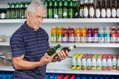 Senior Man Comparing Beer Bottles Stock Photography