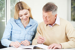 Senior Man Completing Crossword Puzzle With Teenage Granddaughte Stock Images