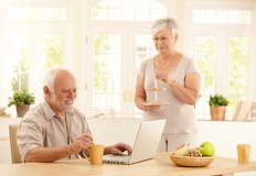 Senior man with computer and coffee in kitchen Royalty Free Stock Images
