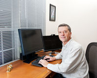 Senior man at computer desk Royalty Free Stock Photography
